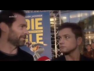 Taron Edgerton stares at Hugh Jackman