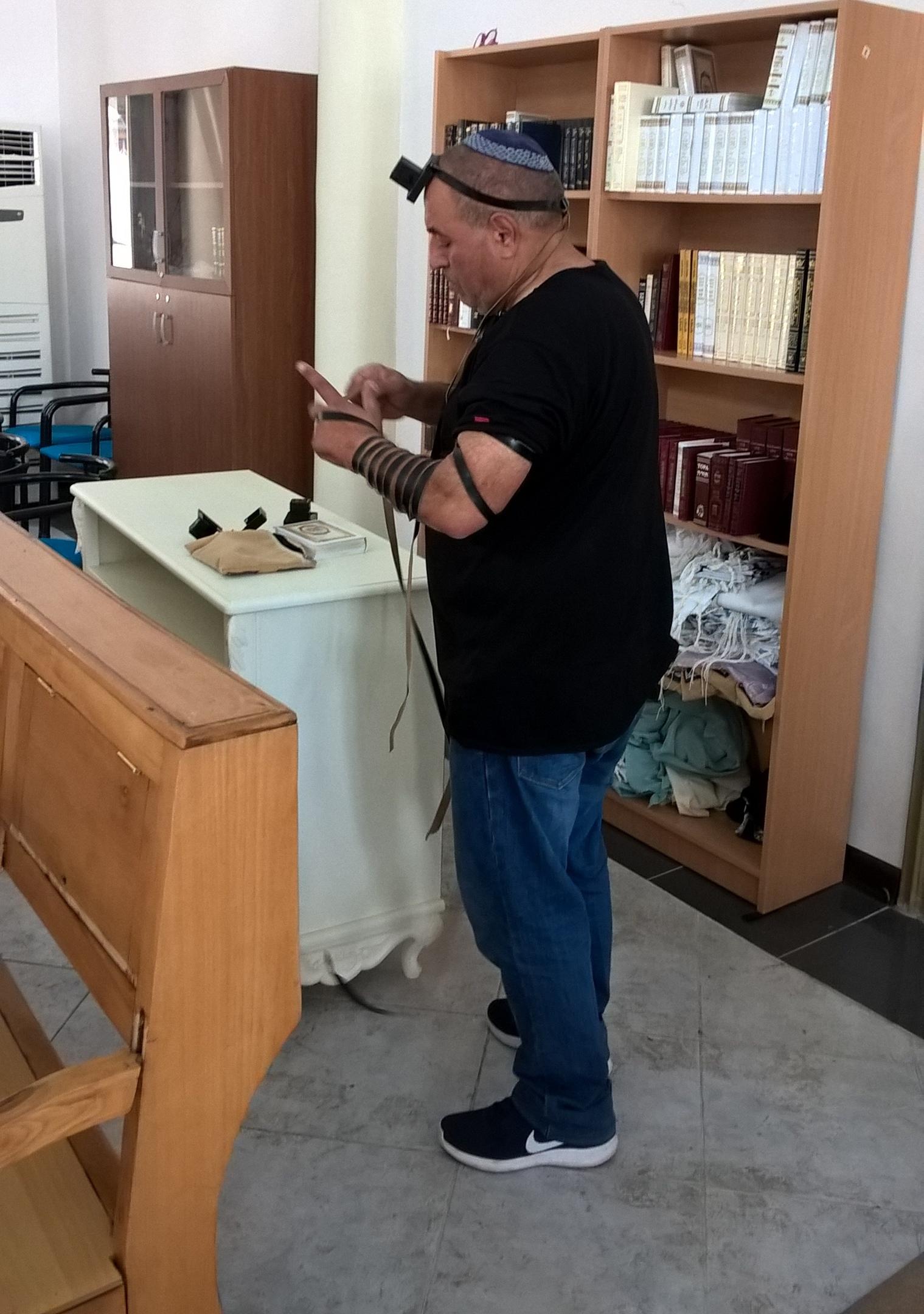 еврей наматывает некую ленту для молитвы